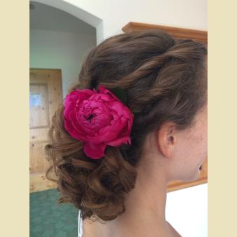 Brautfrisur mit pinkfarbener Blume